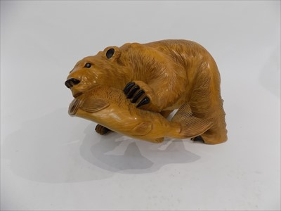 Lot 40-A carved wood sculpture of a bear with a fish in...