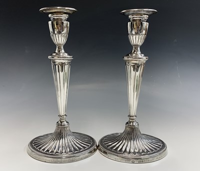 Lot 1083 - A pair of Adam style silver candlesticks by...