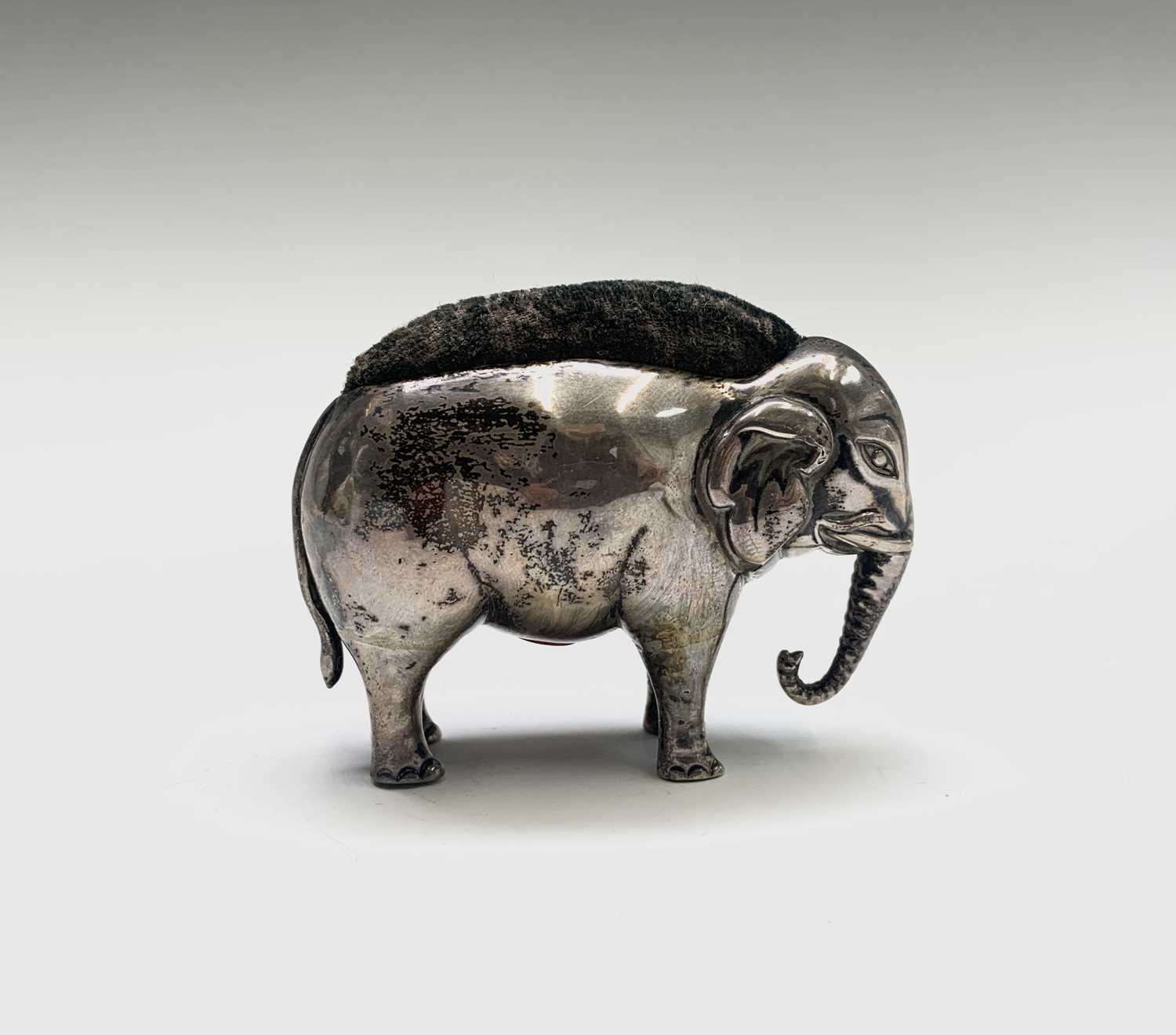 Lot 1079 - An Edwardian silver elephant pin cushion by...