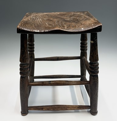 Lot 71 - An elm stool, 19th century, the dished seat on...