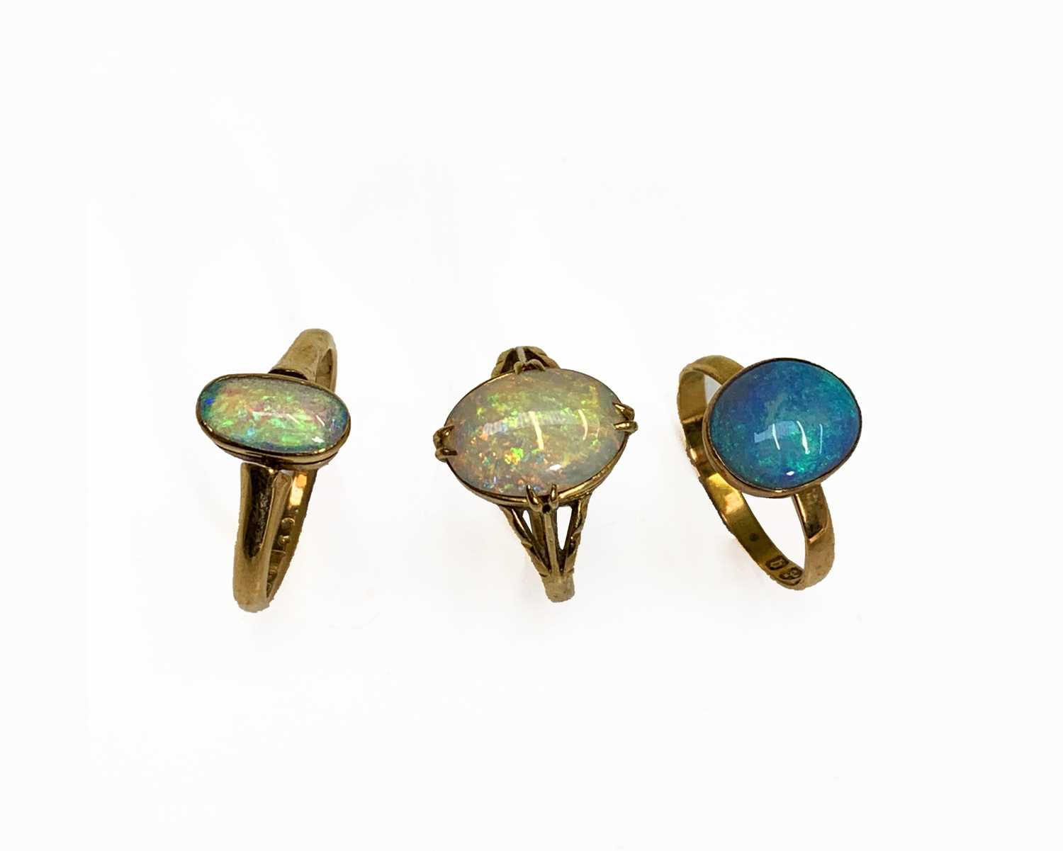 Lot 255 - Three gold rings each with an oval opal 7.9gm