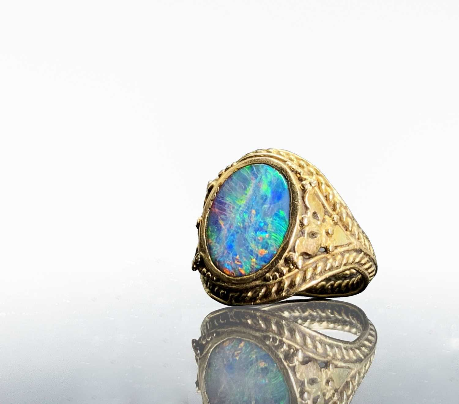 Lot 31 - A gold ring with an opal in ornate pierced and...