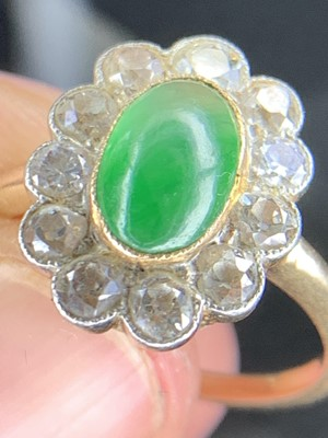 Lot 18 - A cabochon emerald and diamond oval cluster...