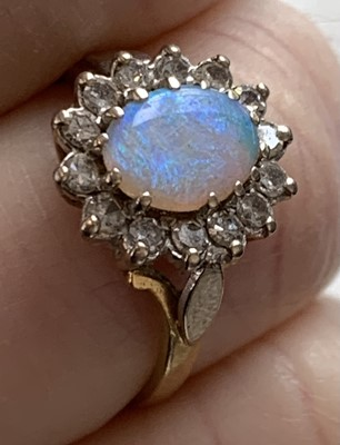 Lot 58 - An opal and diamond oval cluster ring 3.7gm