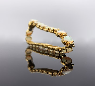 Lot 10 - An 18 ct gold bracelet with twenty opals, each...