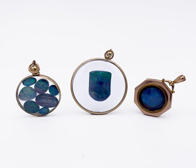 Lot 157 - Three gold-mounted pendants, each containing...