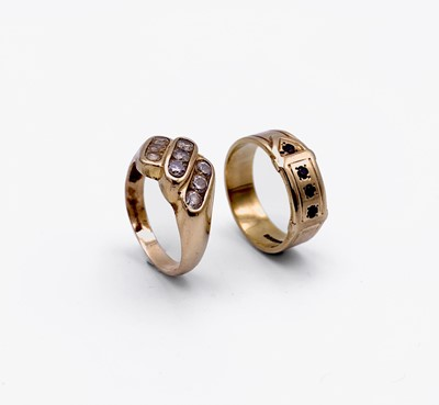 Lot 130 - A 9ct gold buckle ring set with red stones and...
