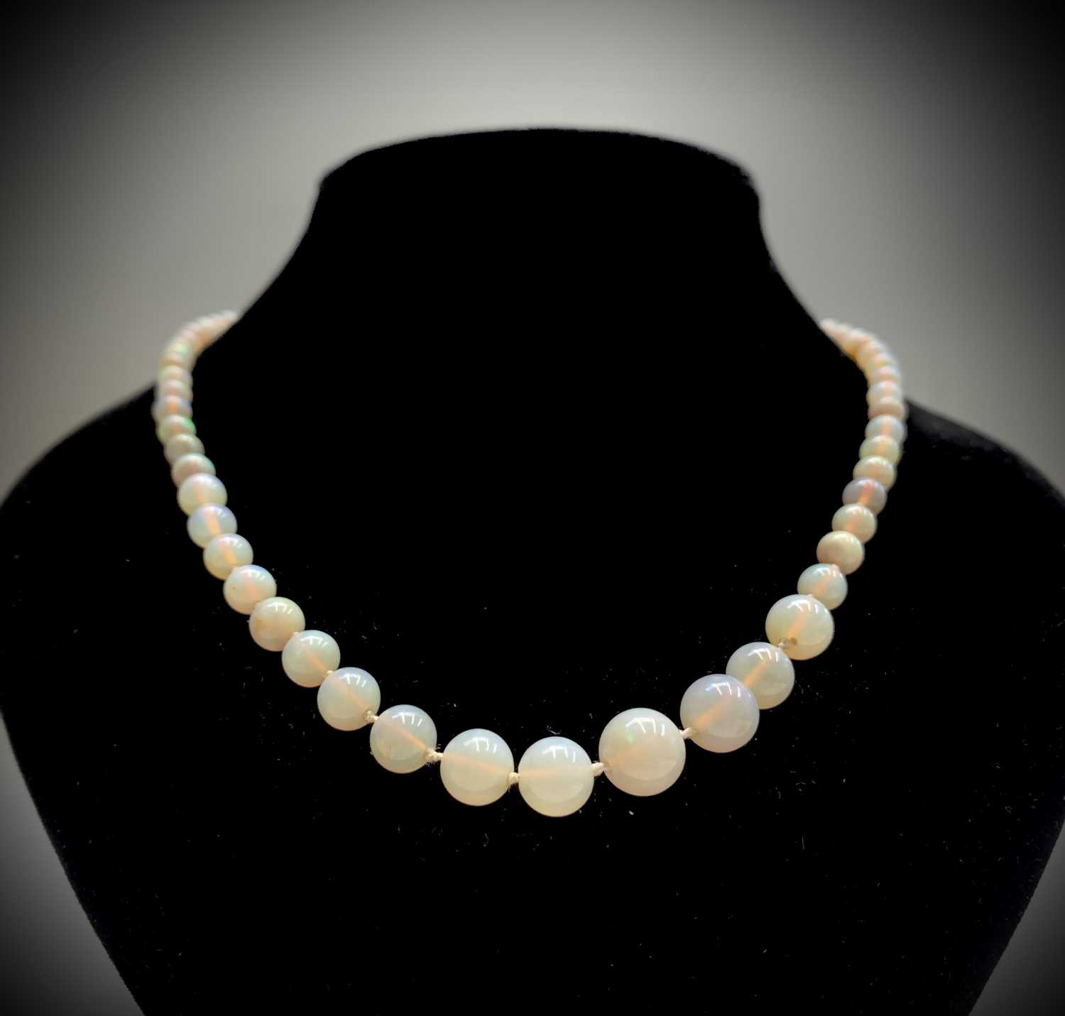 Lot 11 - An opal necklace of 71 graduated beads the...