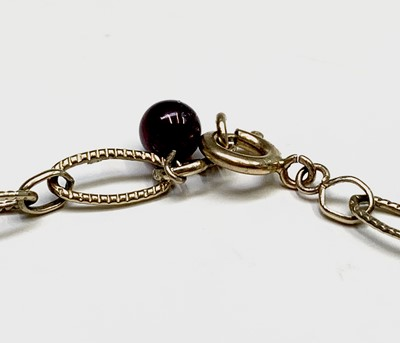 Lot 38 - A 9ct gold bracelet with seven garnet beads 4.7gm
