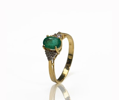 Lot 240 - An 18ct gold ring set with an emerald flanked...
