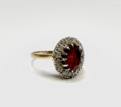 Lot 198 - A gold ring with an oval red stone and diamond...