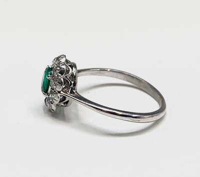 Lot 27 - An 18ct white gold emerald and diamond oval...