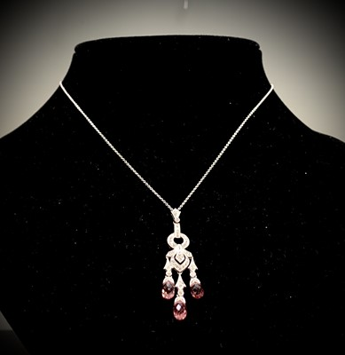Lot 66 - An 18ct white gold pendant and chain set with...