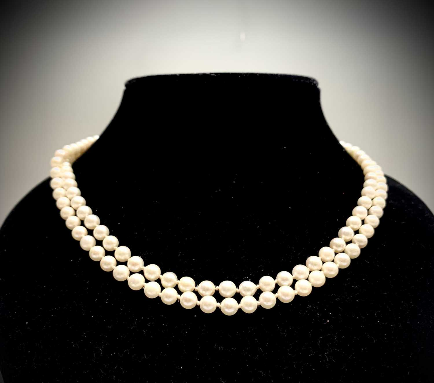 Lot 73 - A double-strand pearl necklace with 14ct...