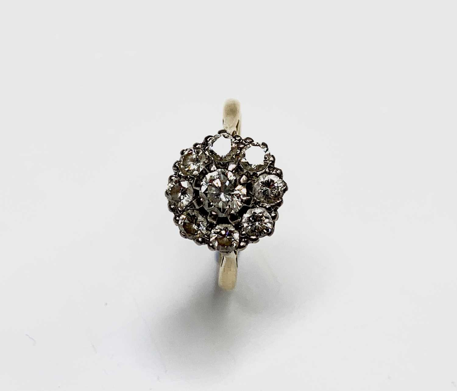 Lot 202 - An 18ct gold ring set a bright nine stone...
