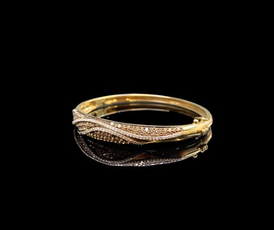 Lot 134 - A gold hinged bangle pave and line set with...