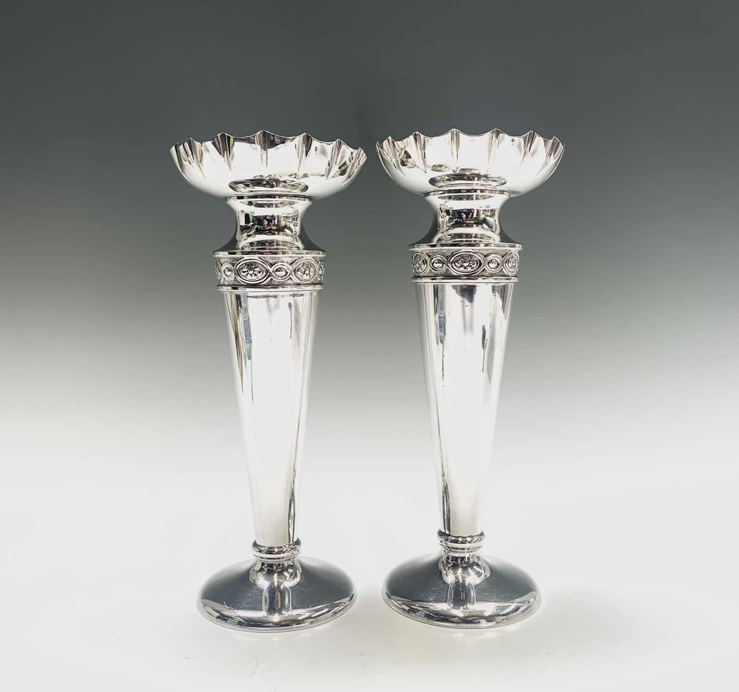 Lot 1010 - A pair of silver vases, the necks with chased...