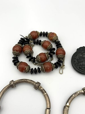 Lot 177 - A Chinese black stone carved pendant 40mm wide,...