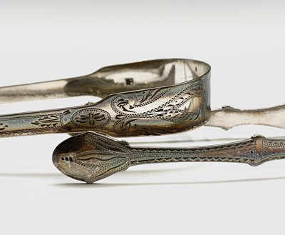 Lot 1028 - Two pairs of silver sugar tongs each by Peter...