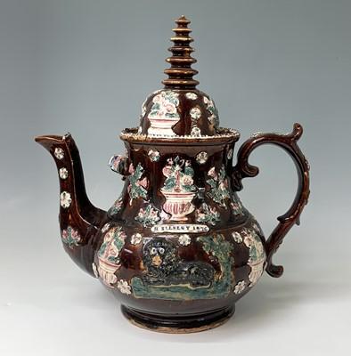 Lot 815 - A Measham treacle glazed barge ware teapot,...