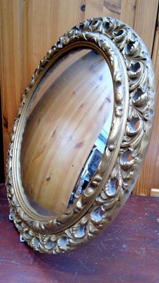 Lot 6 - A circular convex wall mirror with caved and...