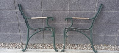 Lot 3 - A pair of cast iron bench ends with wooden arm...