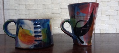 Lot 11 - Two colourful Trevarno studio pottery cups...
