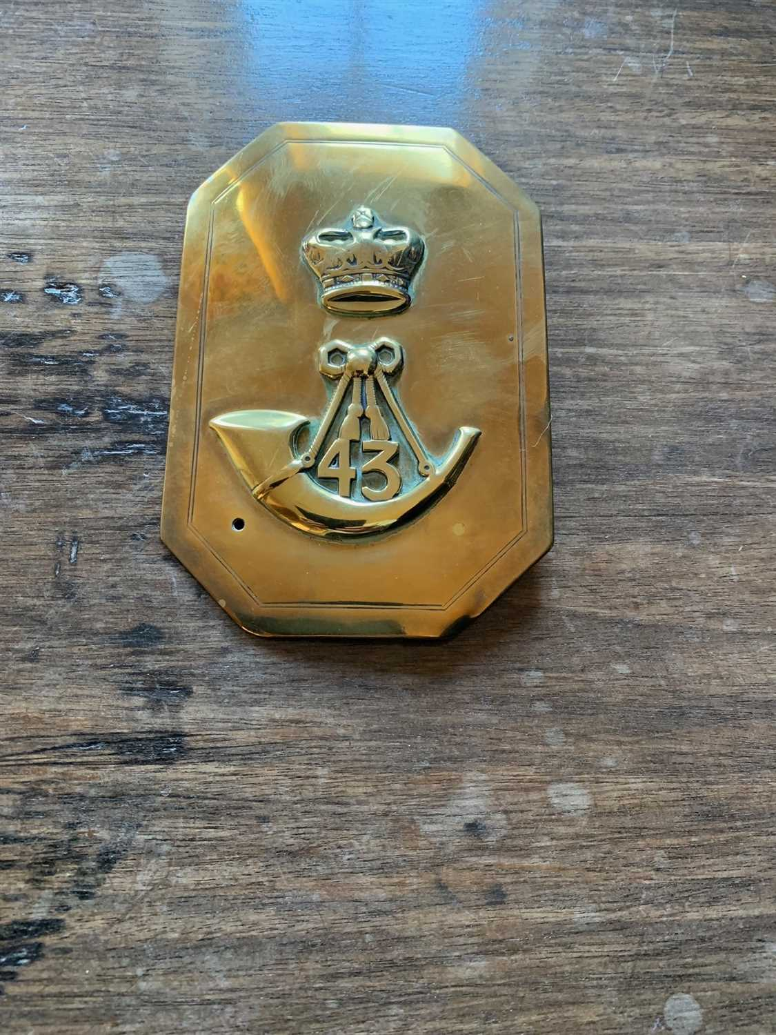 Lot 5-A military brass plate, decorated with a crown...